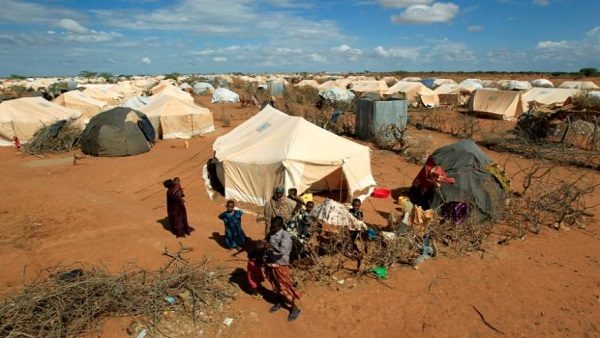 Refugees stand outside their tent at the Ifo Extension refugee camp in Dadaab, near the Kenya-Somalia border in Garissa County, Kenya October 19, 2011. REUTERS/Thomas Mukoya/File Photo