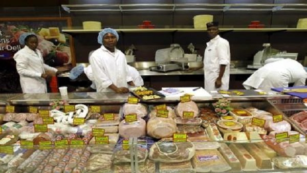 Workers arrange meat products inside a supermarket. File Photo  REUTERS/Thomas Mukoya