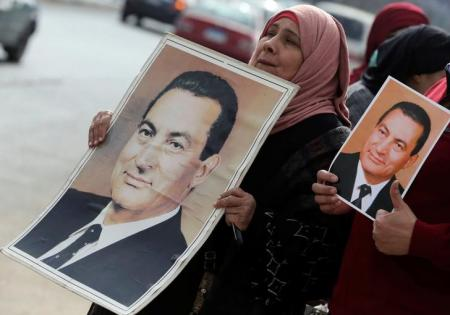 Supporters of former Egyptian President Hosni Mubarak hold up his pictures as they wait for him to be transferred to a court, in front of Maadi military hospital in Cairo, Egypt, March 2, 2017. REUTERS/Mohamed Abd El Ghany