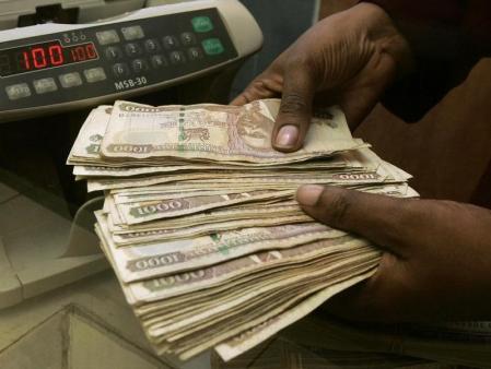 A currency dealer counts Kenya shillings at a money exchange counter in Nairobi, fle. REUTERS/Antony Njuguna