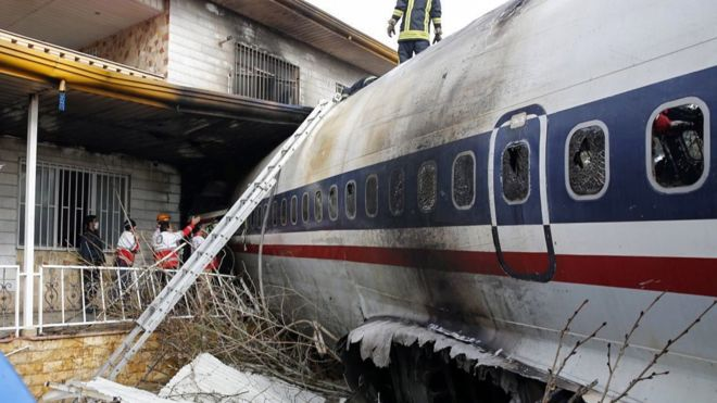 The plane crashed into a wall separating the airport from a residential area and then hit a house. Photo: EPA