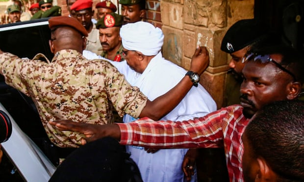 Omar al-Bashir (C) is escorted into a vehicle as he returns to prison. Photo: Ashraf Shazly/AFP/Getty Images