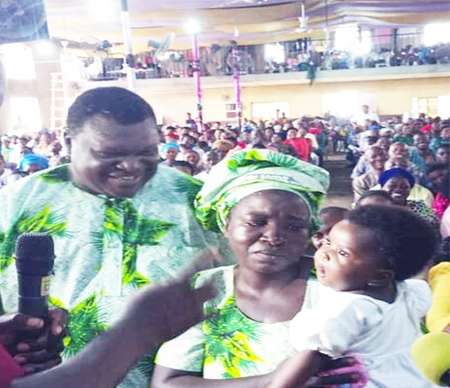 Lola and Abiodun in Church with their baby delivered allegedly after ten years of pregnancy.