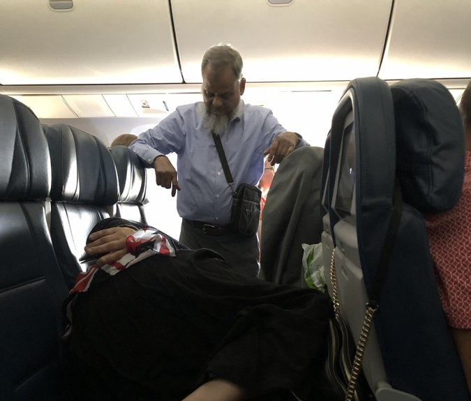 Man stands in plane for wife to sleep